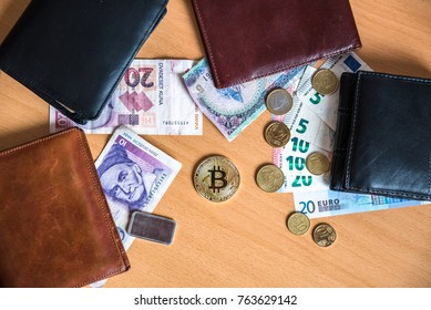Bitcoin coin in physical form. Coin, surrounded with money wallets and old currencies. Euro, Kuna, Deutsche mark.
