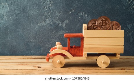 Bitcoin coin in toy truck on wooden table Cryptocurrency concept
