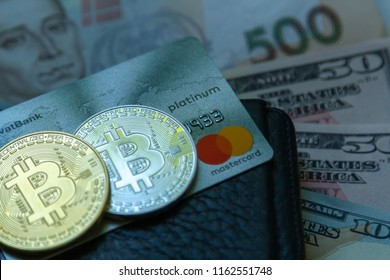Bitcoin coins and bank payment Mastercard card against the background of dollar bills. Bitcoin and Mastercard payment cards. Coins bitcoin, bank card and dollars. Kiev, Ukraine, August 22, 2018