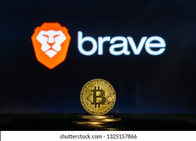 Bitcoin coins with Brave browser logo on a laptop screen. Cryptocurrency and blockchain adoption getting mainstream. Slovenia - 02 24 2019