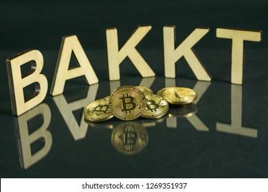Bitcoin coins in front of bakkt sign made of wood with reflection on the table, Slovenia - December 27th