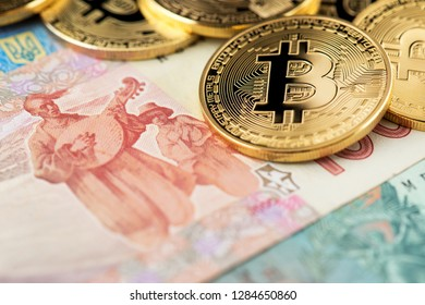 Bitcoin coins new virtual money on Ukraine banknotes close up image of bitcoins with Ukraine hryvnia banknotes Bitcoin coin on the background of Ukraine hryvnia Bitcoin and Ukraine national currency
