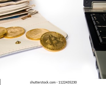 Bitcoin coins on an open wallet, next to a laptop. It symbolizes revenues earned on the Internet.