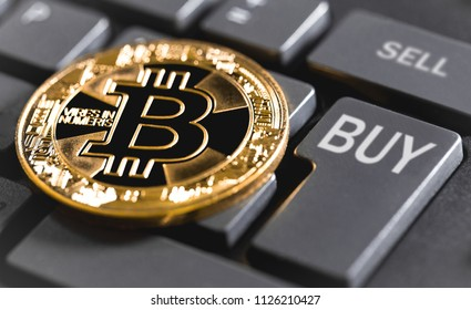 bitcoin and computer keyboard with buttons buy & sell