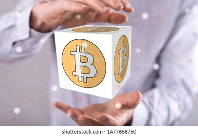 Bitcoin concept between hands of a man in background