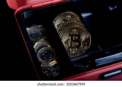 A bitcoin concept of bitcoins in a money box next to regular one poiund coins