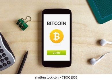 Bitcoin concept on smart phone screen on wooden desk. All screen content is designed by me. Flat lay