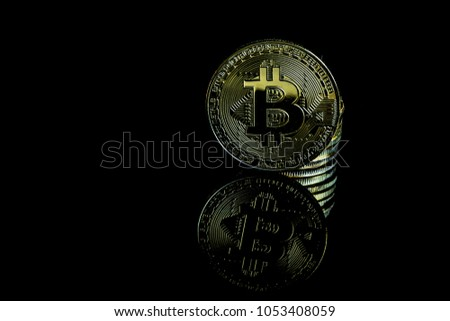 A bitcoin concept with tokens on a black background to represent the dark use of the currency