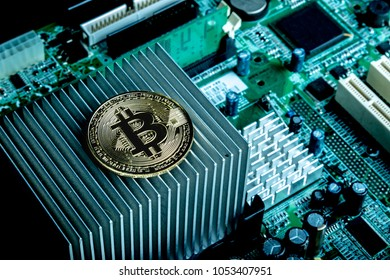 A bitcoin concept with tokens on a computer circuit board showing the currency is virtual