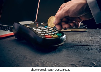 Bitcoin, credit card and POS-terminal. The golden bitcoin in male hands. Cryptocurrency bitcoin coins. Litecoin, Bitcoin, Ethereum, e-commerce, busibess, finance concept. crypto currency symbol