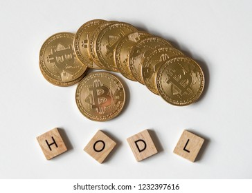 """Bitcoin crypto currency with letter tiles spelling out """"HODL"""" which is insider lingo for """"hold"""", overhead view."""