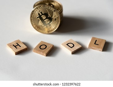 """Bitcoin crypto currency with letter tiles spelling out """"HODL"""" which is insider lingo for """"hold"""", angled view."""