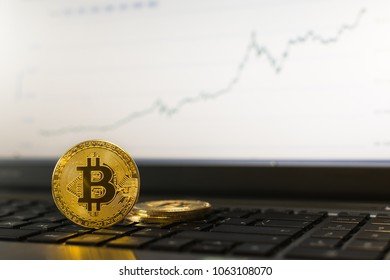 Bitcoin cryptocurrency coin on laptop keyboard, ascending chart on background