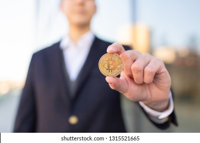 Bitcoin cryptocurrency coin in a young businessman hand. Disruptive blockchain technology concept and transfer of wealth.