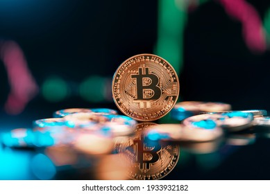 Bitcoin cryptocurrency with colorfull blurred candlestick chart in the background and reflection