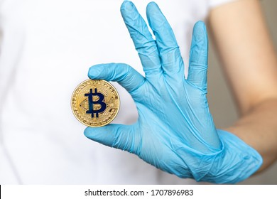 Bitcoin and cryptocurrency during coronavirus pandemic. Golden metal coin showed and held in hands in blue disposable protective rubber gloves
