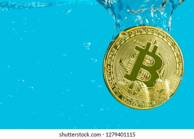 bitcoin cryptocurrency gold coin falls into the water with bubbles drowning on a blue background
