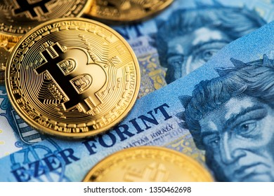Bitcoin Cryptocurrency on Hungarian Forint banknotes close up image. Cryptocurrency Bitcoin virtual money with Hungarian Forint money. Hungary Bitcoin Forint Cryptocurrency Blockchain BTC