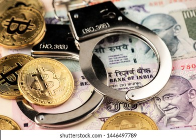 Bitcoin Cryptocurrency on Indian money Rupee banknotes and police handcuffs. Close up image of Bitcoin with Indian Rupee and police handcuff. Bitcoin Cryptocurrency against money from India. India