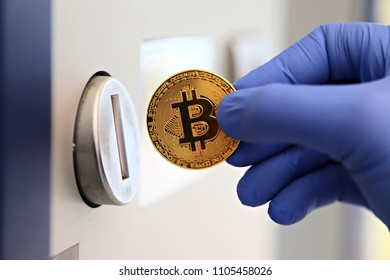 Bitcoin cryptocurrency payments. Hand in a blue glove putting gold bitcoin coin into a coin slot, shallow focus