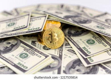 Bitcoin crypto-currency stacked with 100 dollar bills, close up isolated, room for text of background image.
