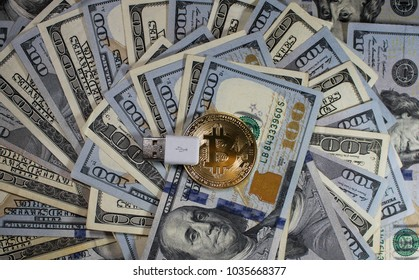 Bitcoin Cryptocurrency USB assembled on top of hundred dollar bills