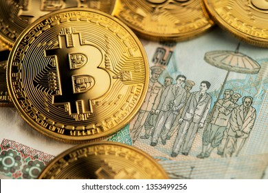 Bitcoin cryptocurrency virtual money and banknotes of Thai Baht. Background with crypto Bitcoin and Thai Baht. Bitcoin Cryptocurrency on Thailand Baht banknotes close up image.