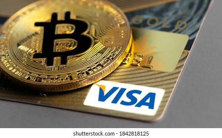 bitcoin cryptocurrency with Visa credit card. Visa - American multinational company providing services of payment operations. Moscow, Russia - August 16, 2020
