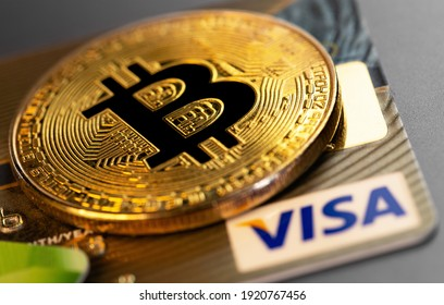 bitcoin cryptocurrency and Visa plastic electronic card closeup. Visa - American multinational company providing services of payment operations. Moscow, Russia - January 18, 2021