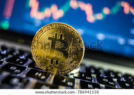 Bitcoin currency with blockchain concept on laptop keyboard with coins and charts and graphs. Crypto investment security and strategy.