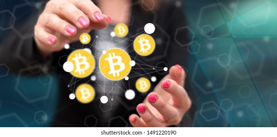 Bitcoin currency concept between hands of a woman in background