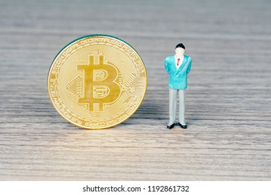 Bitcoin digital decentralised peer to peer on a wooden table and miniature figure side by side
