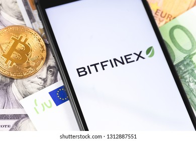 Bitcoin, dollars, euro banknotes and Bitfinex logo of exchange on the screen smartphone. Bitfinex is cryptocurrency exchange on the market. Moscow, Russia - February 13, 2019