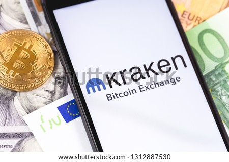 Bitcoin, dollars, euro banknotes and Kraken logo of exchange on the screen smartphone. Kraken is cryptocurrency exchange on the market. Moscow, Russia - February 13, 2019