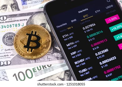 bitcoin, dollars, euro and smartphone with cryptocurrency stock market closeup. Moscow, Russia - December 4, 2018