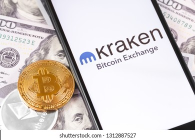 Bitcoin, dollars and Kraken logo of exchange on the screen smartphone. Kraken is popular largest cryptocurrency exchange on the market. Moscow, Russia - February 13, 2019