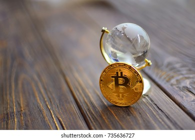 Bitcoin and the economy of the world concept. Coin bitcoin is based on a small glass globe. World economy background.