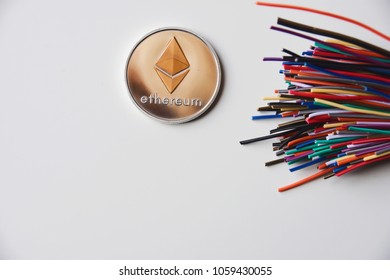 Bitcoin and Ethereum (BTC, ETH) crypto currency coins on the top of colorful bundle of cables/wires on a white background.