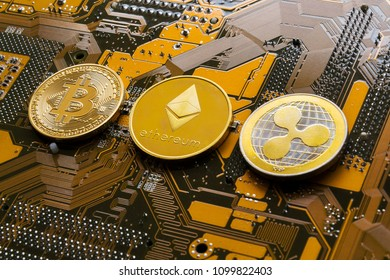 Bitcoin, Ethereum and Ripple coins - largest cryptocurrencies by market capitalization lying on computer motherboard, cryptocurrency investing concept