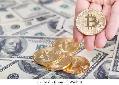 Bitcoin in female hand on dollar banknotes background, closeup