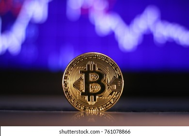 A Bitcoin in front of a blurred share price. Bitcoin is a decentralised payment system.