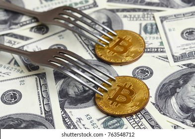 Bitcoin getting New Hard Fork Change, Physical Golden Crytocurrency Coin under the fork on the dollars background. Blockchain Transaction System Crisis Concept