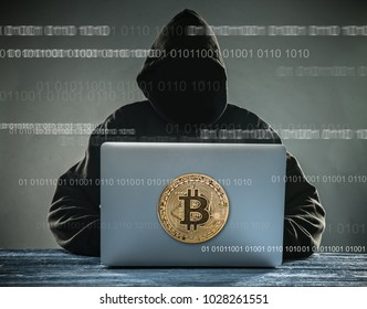 Bitcoin gold coin and anonymous hacker sittign with laptop. Virtual danger of cryptocurrency.