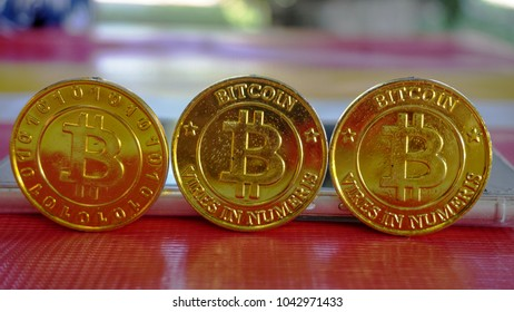 Bitcoin gold coin and blurred nature background. Virtual cryptocurrency concept