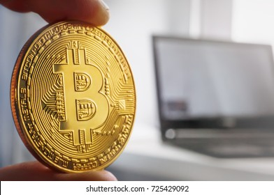 Bitcoin gold coin in the hand of man on the background of the laptop on a white table.