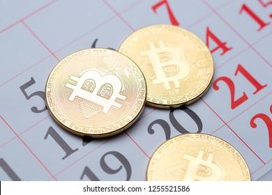 Bitcoin gold coins lying on the calendar.