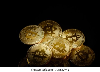 Bitcoin gold coins on black background. Cryptocurrency content.