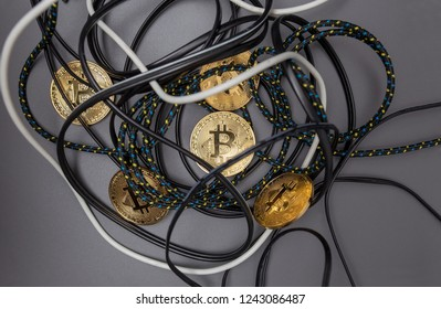 Bitcoin gold coins trangled in a nest of cables on a grey background
