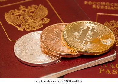 Bitcoin gold, silver and bronze coin on Russian passport.