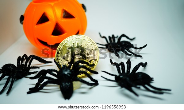 Bitcoin golden coin with plastic spiders and a plastic pumpkin baskets for trick and treat. White background